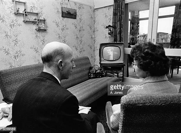 A couple watching television in their sitting room