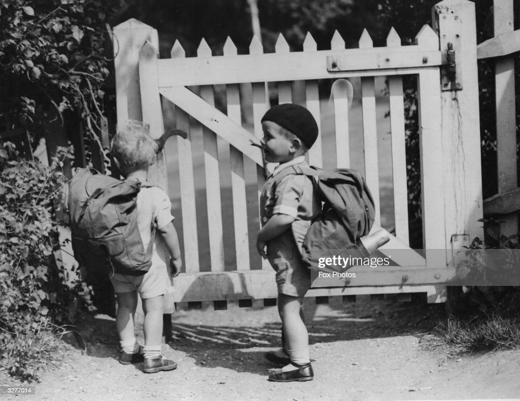 Two young children with back-packs about to open a gate.