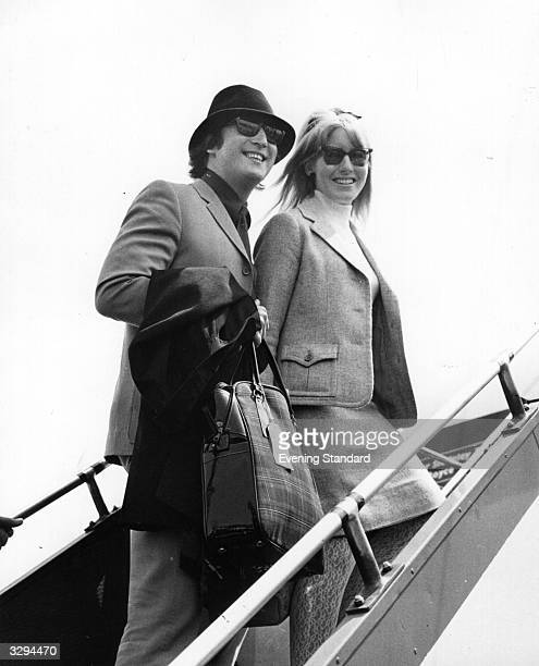 Beatle John Lennon and his wife Cynthia boarding an aeroplane at London Airport