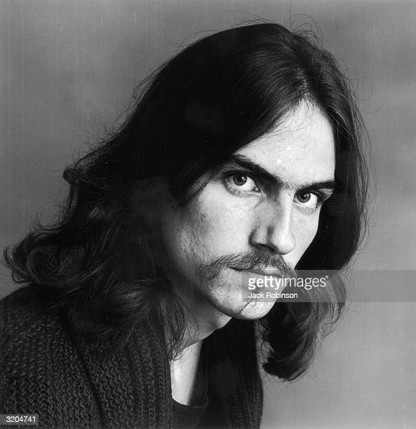 Headshot portrait of American folk musician James Taylor looking at the camera wearing a black sweater