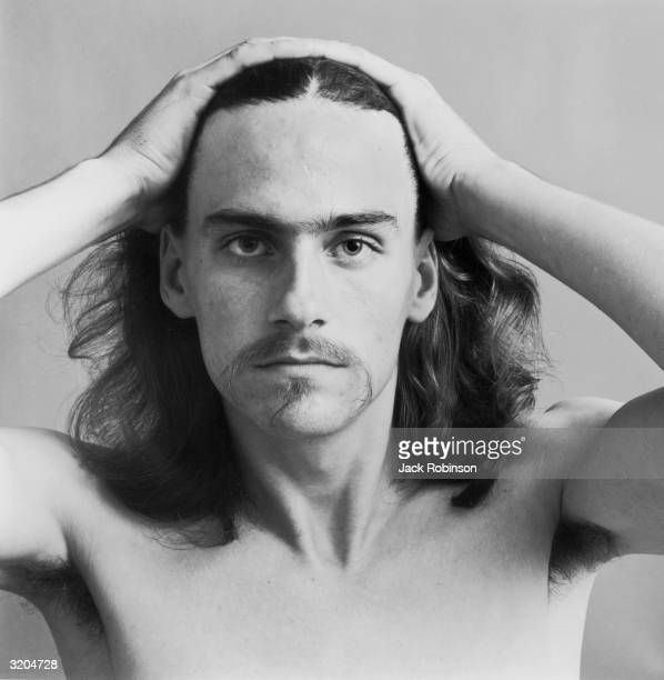 Headshot portrait of American folk musician James Taylor pulling his hair back with his hands He is bare chested