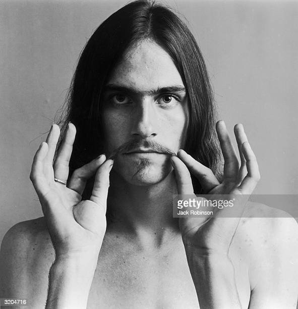 Headshot portrait of American folk musician James Taylor holding the ends of his mustache He is bare chested