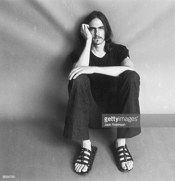 Portrait of American folk musician James Taylor sitting on the floor with his knees pulled up to his chest and his head resting on his hand He wears...