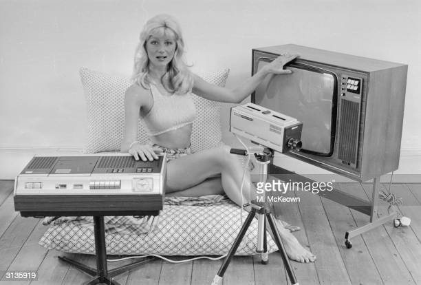 A scantilyclad woman displaying a video recorder a camera and a television set