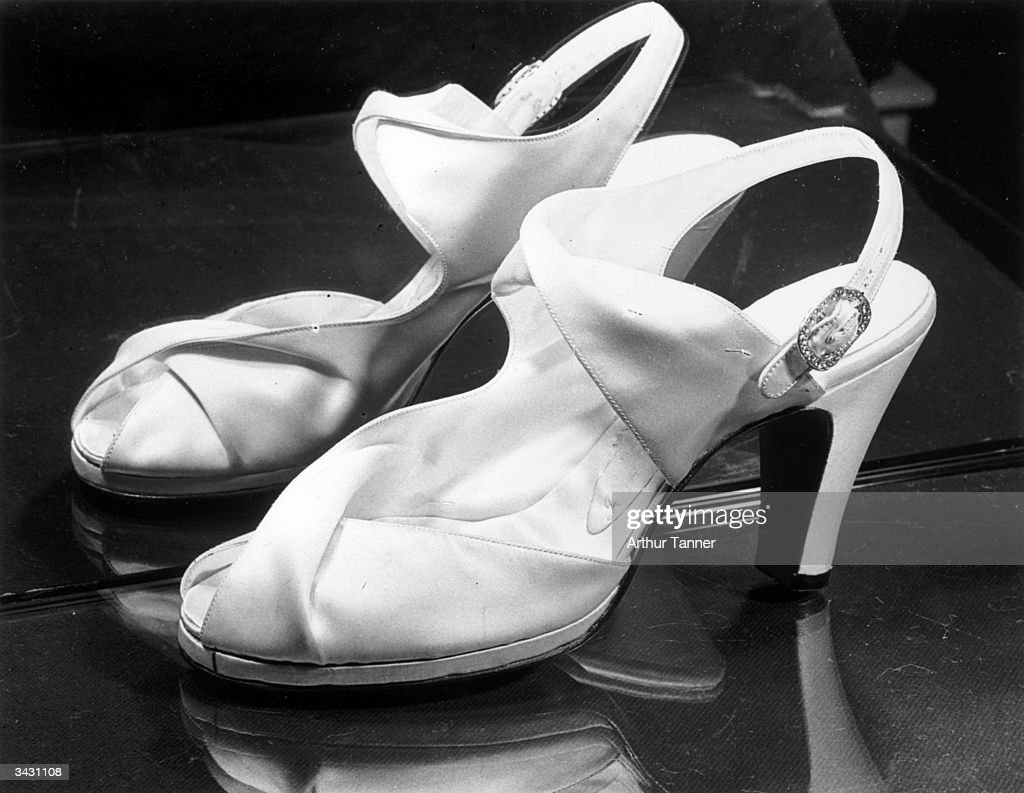 Shoes worn by Princess Elizabeth (Queen Elizabeth II) on her wedding day. Ivory duchesse satin self-lined, they are in one piece, embracing the waist of the foot with reverse folds on the high instep strap and across the front. The draped sandals are finished off with a silver buckle studded with small pearl.