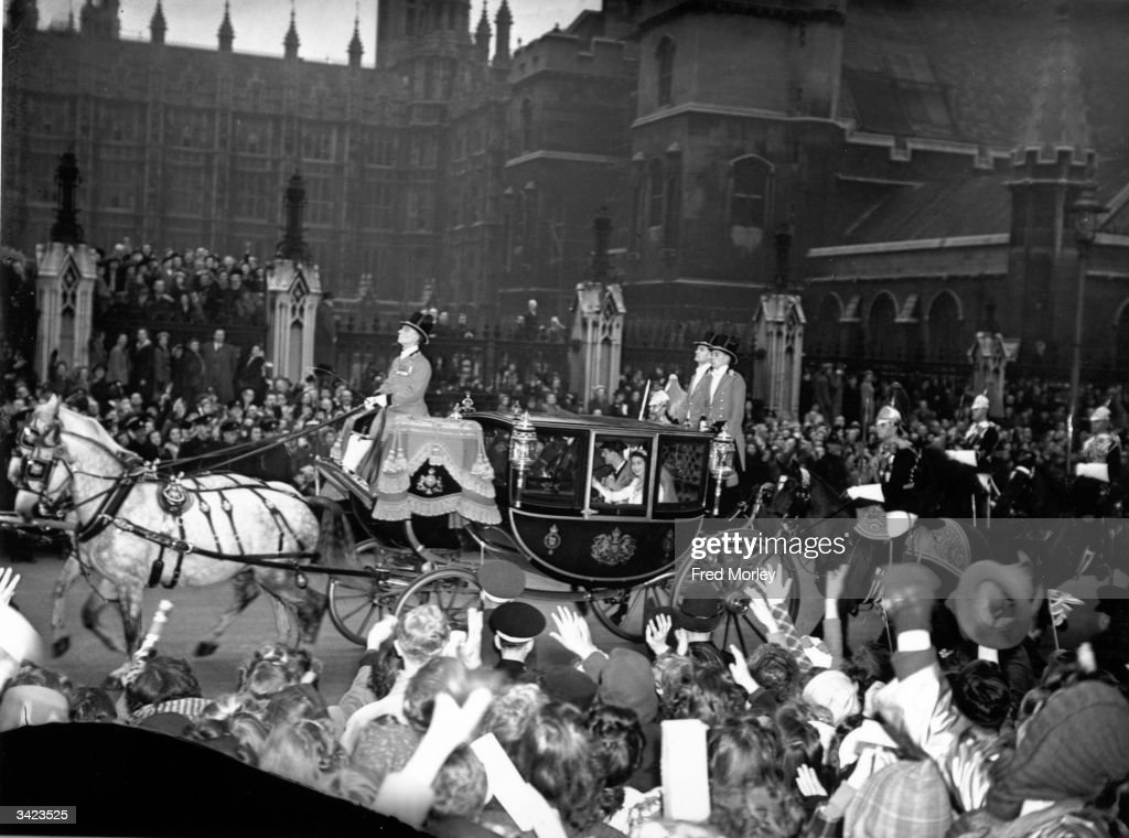 The newly married Princess Elizabeth and Prince Philip of Greece, wave from the royal carriage as the Royal Wedding Procession passes through the cheering crowds at Parliament square.