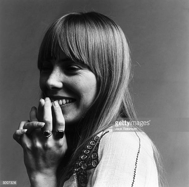 Headshot portrait of American musician Joni Mitchell smiling with her hands over her mouth This image was from a photo shoot for the fashion magazine...