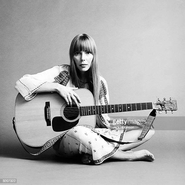 Portrait of American musician Joni Mitchell seated on the floor with her acoustic guitar in her lap This image was from a shoot for the fashion...