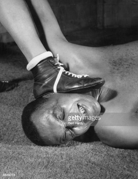 Canadian wrestler and former Empire heavyweight boxing champion Larry Gains has his face trodden on during a training bout at the Imperial Hotel...