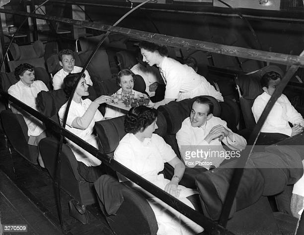 Trainee BOAC cabin crew members during training acting the parts of passengers in a replica of a Hermes aircraft near Heston Airport Middlesex...