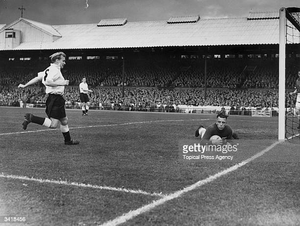 Canadian national goalkeeper Hanson saves from the on rushing England inside right Wilf Mannion as the Touring Canada side play England's World Cup...