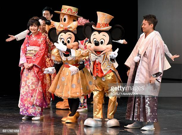 20yearold men and women draped in traditional kimonos are celebrated by Mickey Mouse and Minnie Mouse during their 'ComingofAge Day' ceremony at the...