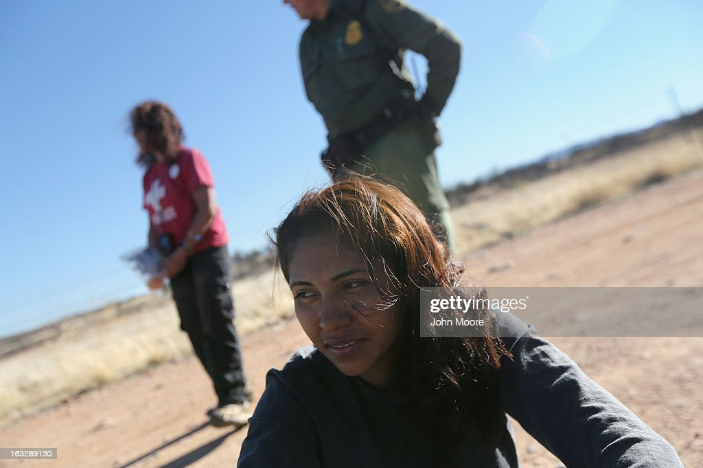 A 20-year-old Mexican immigrant sits under U.S. Border Patrol supervision after her group was caught after crossing into the United States on March 6, 2013 near Walker Canyon, Arizona. Elisa Hauptman (L), a volunteer for the non-profit Samaritans group, arrived to offer water to the detained immigrants. Due to broad federal sequestration budget cuts, Border Patrol agents are expected to begin taking unpaid furlough days in April, as Customs and Border Protection funding is expected to be reduced by more than $500 million.