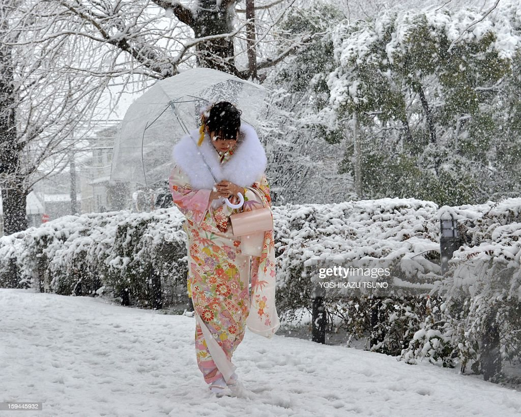 A 20-year-old woman dressed in a kimono walks on a snow covered street to attend a coming-of-age ceremony in Tokyo on January 14, 2013. A storm system grasped central Japan on January 14, causing heavy snow fall around the Japanese capital. AFP PHOTO / Yoshikazu TSUNO