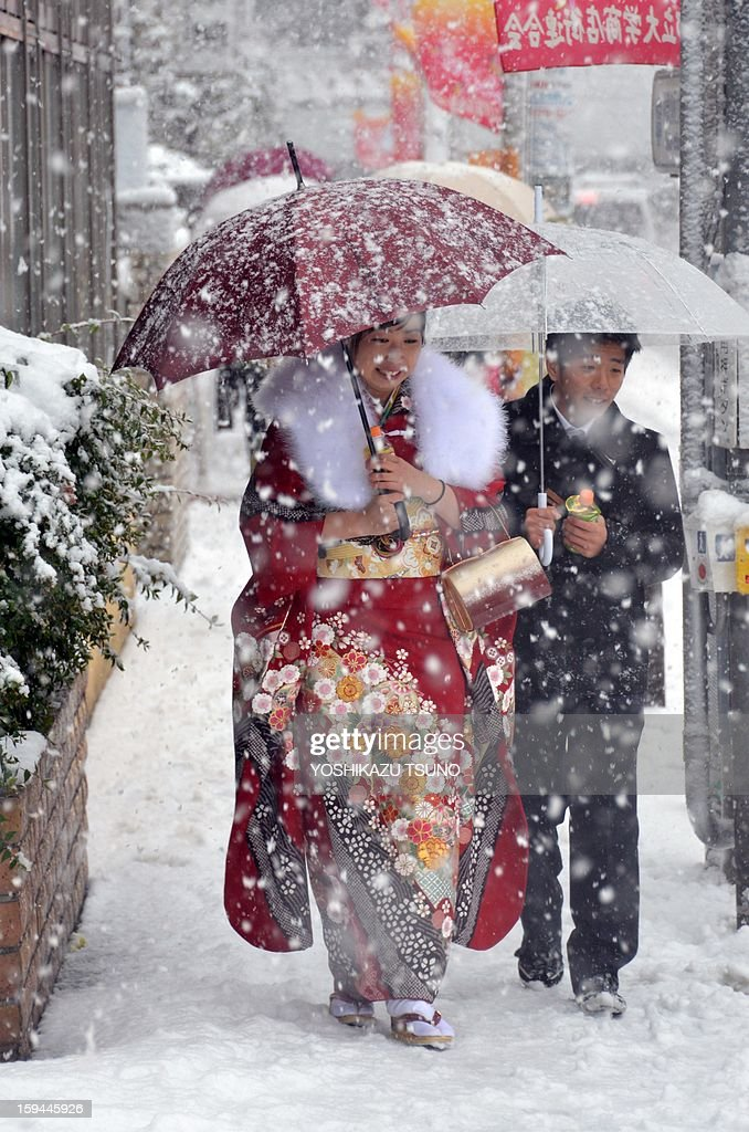 A 20-year-old women dressed in kimono walks on a snow covered street to attend a coming-of-age ceremony in Tokyo on January 14, 2013. A storm system grasped central Japan on January 14, causing heavy snow fall around the Japanese capital. AFP PHOTO / Yoshikazu TSUNO