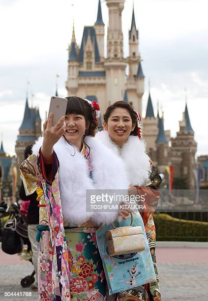 20yearold women in Kimono take a selfie during their 'ComingofAge Day' celebration at Tokyo Disneyland in Urayasu eastern suburb of Tokyo on January...