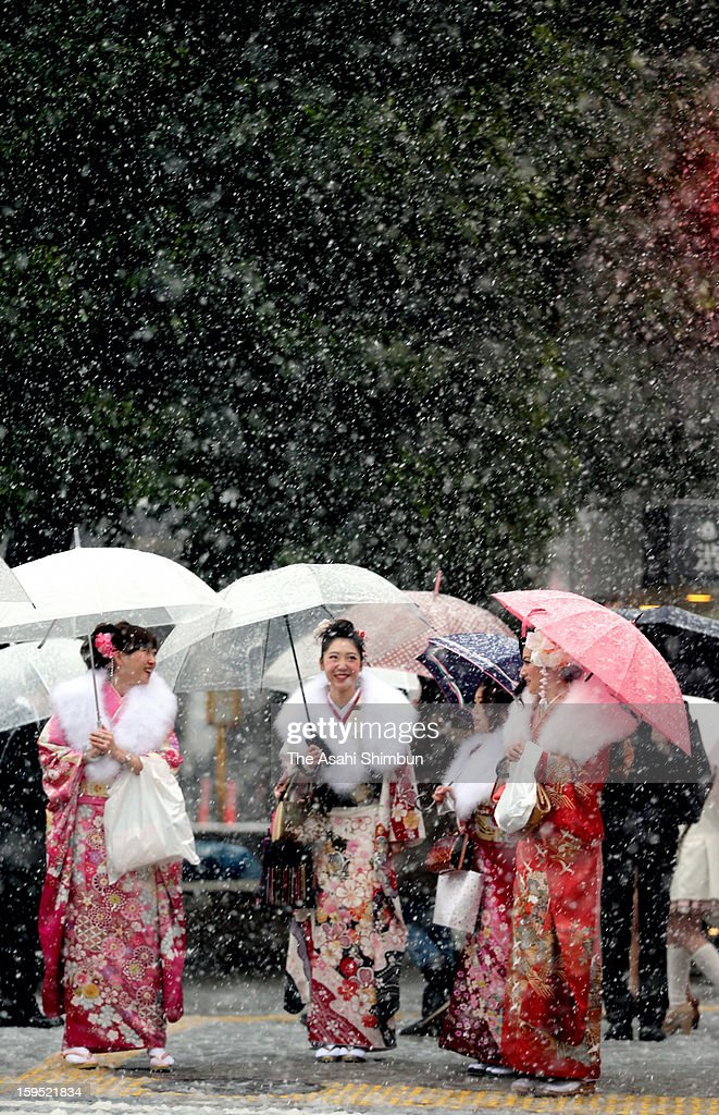 20-year-old women wearing Kimono walk at Shibuya crossing after attending the Coming-of-age ceremony on January 14, 2013 in Tokyo, Japan. A strong low pressure system caused heavy snow and strong wind in the coast area including Tokyo, more than 500 injured.