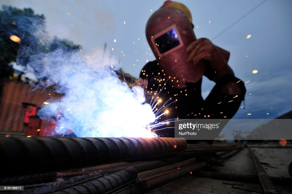 CHAUDHARY, 20yrs old migrated from sunsari, welding iron piler for on-going Bridge expansion work supported by China AID at Kalanki, Kathmandu, Nepal on Monday, July 17, 2017. The workers used to earn daily wage of NRs. 800 (US$ 8) per day.