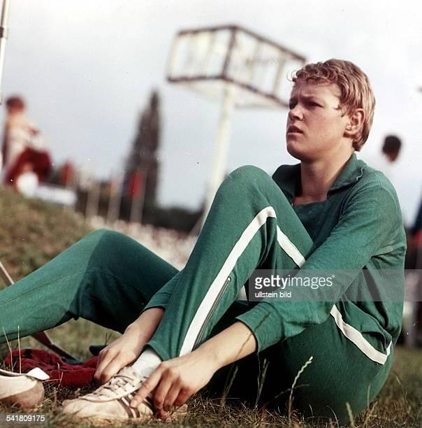 Sportlerin Leichtathletik DDRdie Hochspringerin im Trainingsanzugsitzend auf dem Rasen oJ