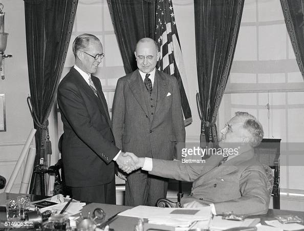 2/18/1938Washington DC With President Roosevelt looking on Joseph P Kennedy former Chairman of the US Maritime Commission is pictured above being...