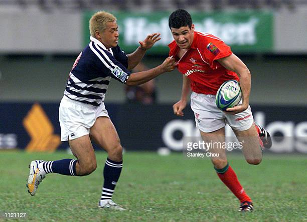 Mike Phillips of Wales breaks away from Yohei Shinomiya of Japan during the Singapore Sevens Bowl final between Wales and Japan during the IRB World...