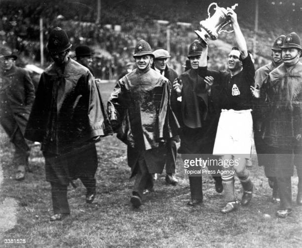 Shepherded by policemen the Blackburn Rovers team captain H Healess carries the FA Cup trophy on a lap of honour around Wembley stadium after his...