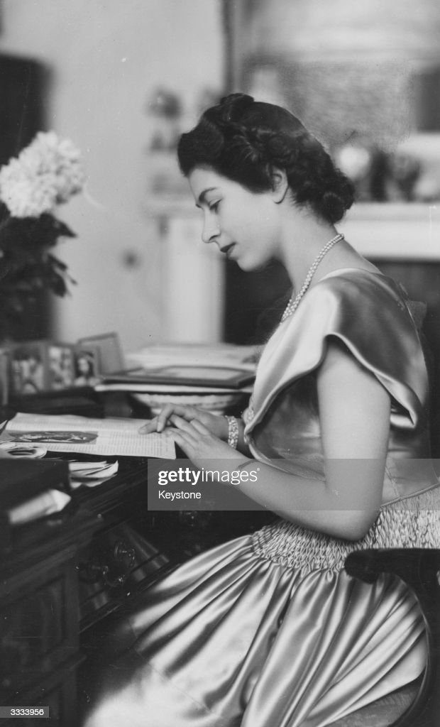 Princess Elizabeth wearing a satin dress at her desk in Buckingham Palace.