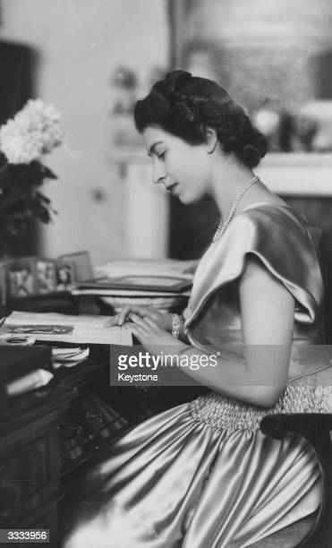 Princess Elizabeth wearing a satin dress at her desk in Buckingham Palace