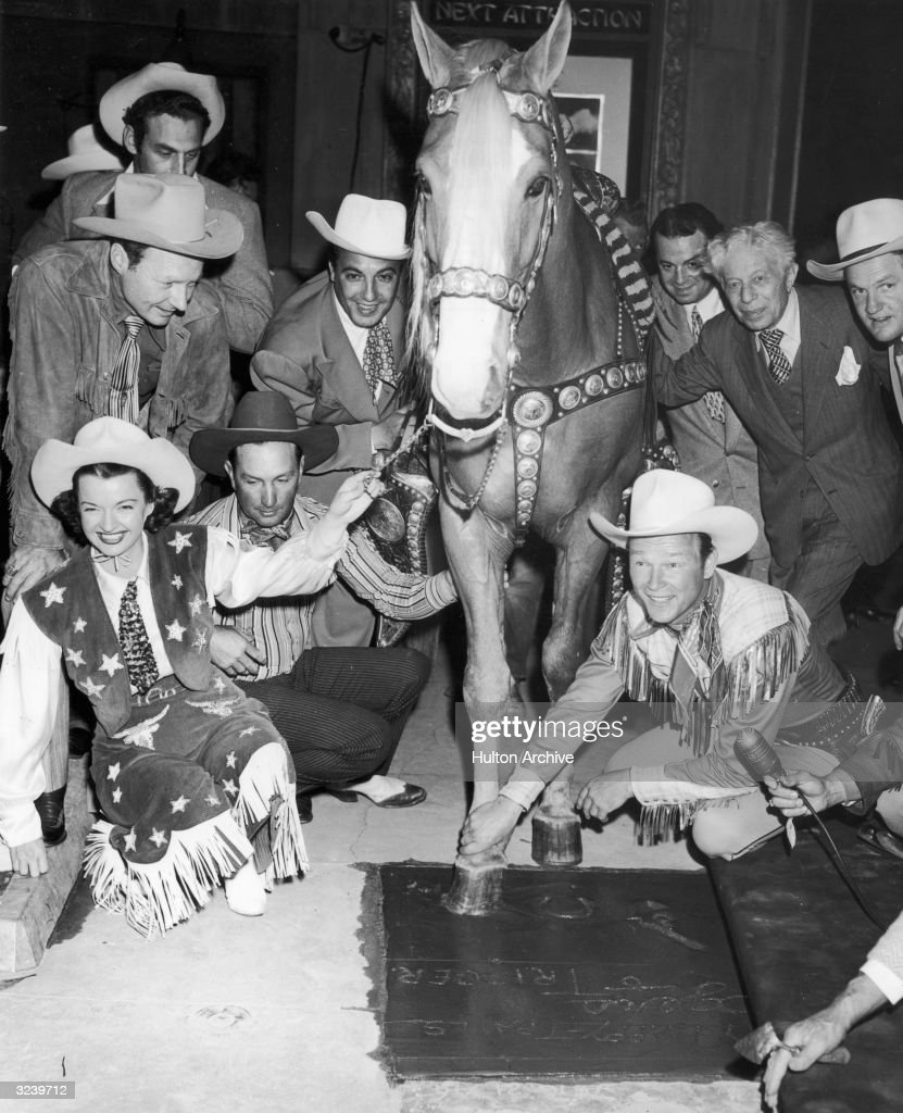 American actor and singer Roy Rogers (1911 - 1998) helps his horse Trigger make a hoof print in the cement as his wife Dale Evans (1912 - 2001) holds the horse's bridle, during a ceremony in front of Mann's Chinese Theater, Los Angeles, California. Rogers and Evans are dressed in Western gear and surrounded by a crowd of onlookers, some of whom are wearing cowboy hats.