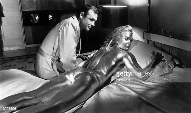 Sean Connery sitting beside his costar English actress Shirley Eaton covered in gold during the filming of a scene from the James Bond film...