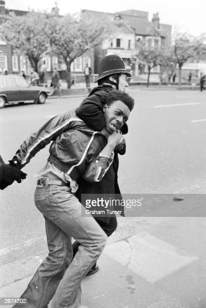 A policeman drags away an arrested protester at a demonstration against the extreme rightwing National Front party in Lewisham London