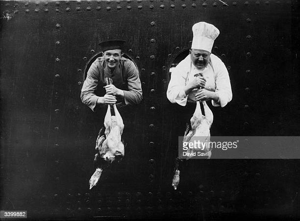 The ship's chef and a kitchen worker displaying the Christmas turkeys through portholes on the PO liner 'Viceroy of India' at Tilbury Essex