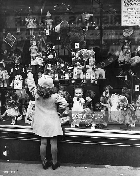 A young girl points at the doll she wants for Christmas in the window of a toy shop