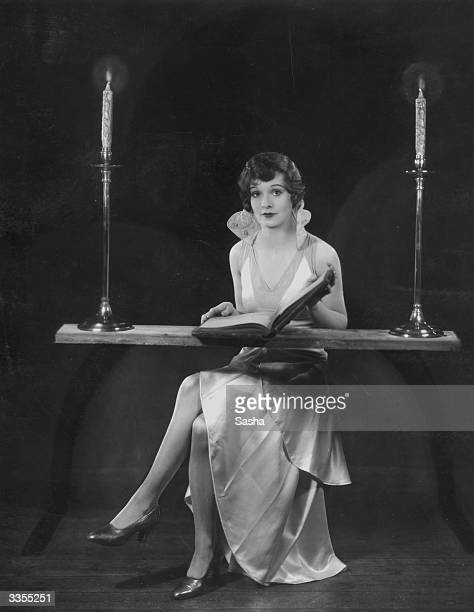 Actress Jean Jay sits reading an old book by candlelight in the dress she is to wear at a Stage Guild Mask Ball in March