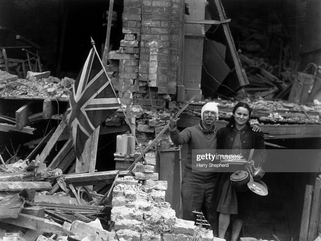 Mr and Mrs Jack Benedy remain cheerfully defiant, whilst standing amidst the wreckage of their home in Turnham Green, London. The house was destroyed during a World War II air raid, and Mr Benedy gives his own version of Churchill's V-sign to the Germans.