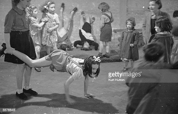 A girl balancing on her hands for a wheel barrow race with a friend while others practice handstands against the wall during the letting off steam...