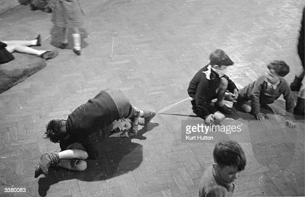 A group of boys play fighting on the floor of Mansford Youth Club in Bethnal Green which has been opened to the under fifteens for one night a week...