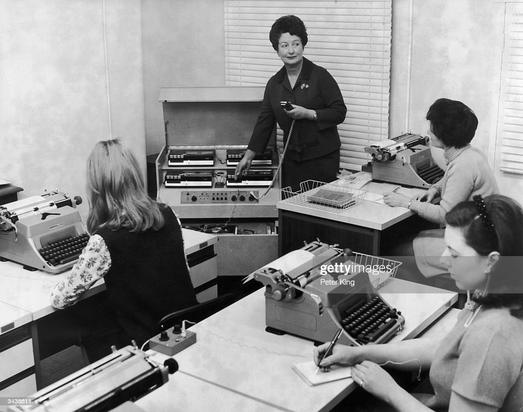 Mrs Lane, Principal of the first Margery Hurst College for Administrative and Secretarial Duties in London, uses Phillips stenolab equipment to train a group of students in taking dictation.