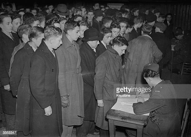 A crowd of young men enlisting forservices in the Forces at a centre in Manchester during WW II