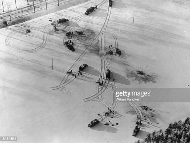 US military vehicles circumvent shell craters in a snowy field in the Ardennes battle sector bringing supplies and ammunition to the front