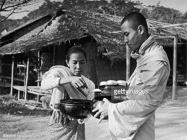 A Burmese monk receiving food from a local village woman The monks have no money and rely upon food that is given to them for their one meal of the...