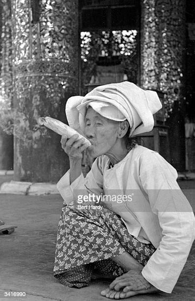 A Burmese woman smoking a large hand rolled cigarette Original Publication Picture Post 4748 Inside The Temples Of Burma pub 1950