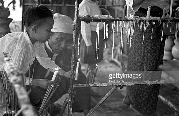 A young child placing a candle and incense on the altar at a Buddhist temple Original Publication Picture Post 4748 Inside The Temples Of Burma pub...