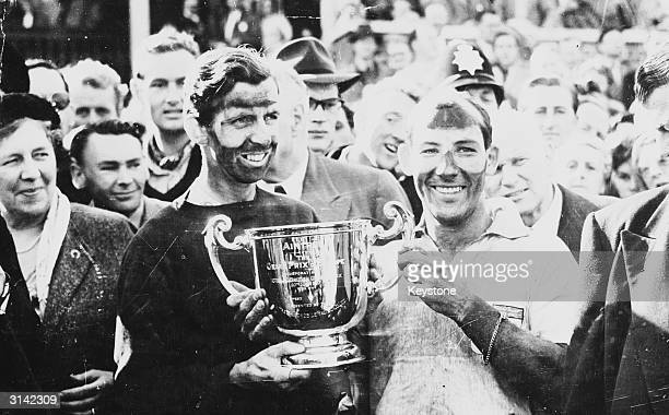 Stirling Moss and his teammate Tony Brooks holding up the Grand Prix Cup after winning the British Grand Prix at the Aintree motor circuit Liverpool