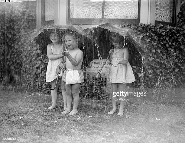 Children at the Barnardo's orphanage at Barking in Essex take shelter under umbrellas during a summer shower