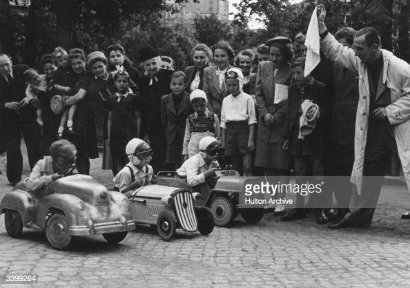 A children's pedal car race set in Berlin zoo being started by German film star Erich Fiedler Friends and family offer support