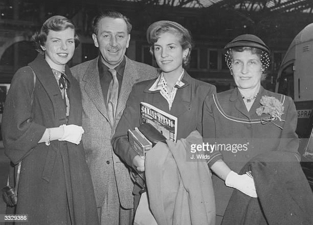 Walt Disney creator of Mickey Mouse with his wife and two daughters at Waterloo station after arriving on the Queen Mary boat train