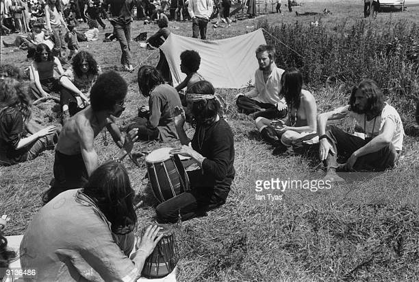 Hippies at the second Glastonbury Festival celebrate the summer solstice with music