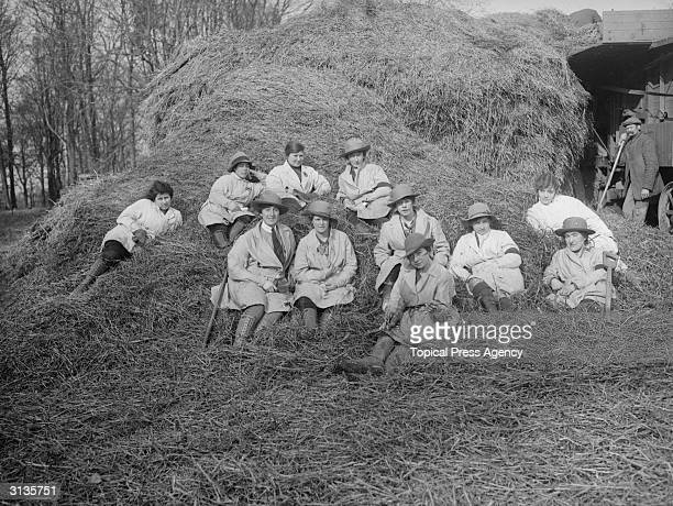 Women during training to be Land Girls take a break in a haystack