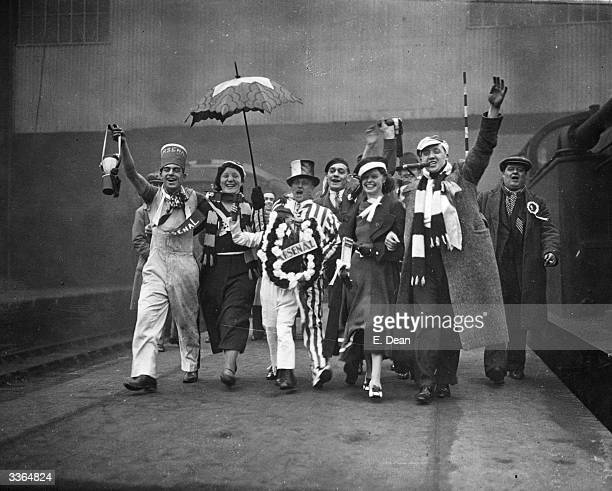 Arsenal football supporters cheer on the platform at King's Cross Station London as they make their way to Huddersfield for their team's FA Cup...